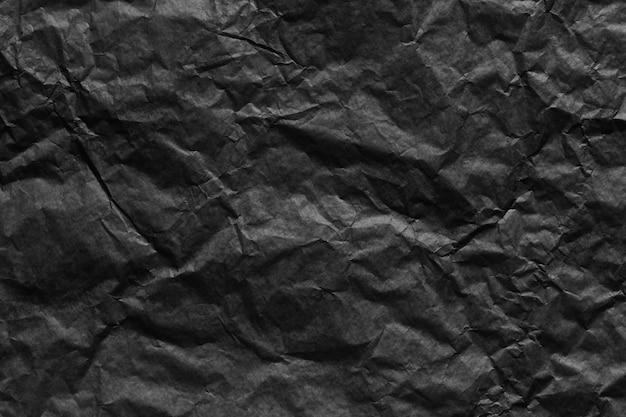 Zwart papier gerimpelde textuur achtergrond voor ontwerp in uw werkconcept.