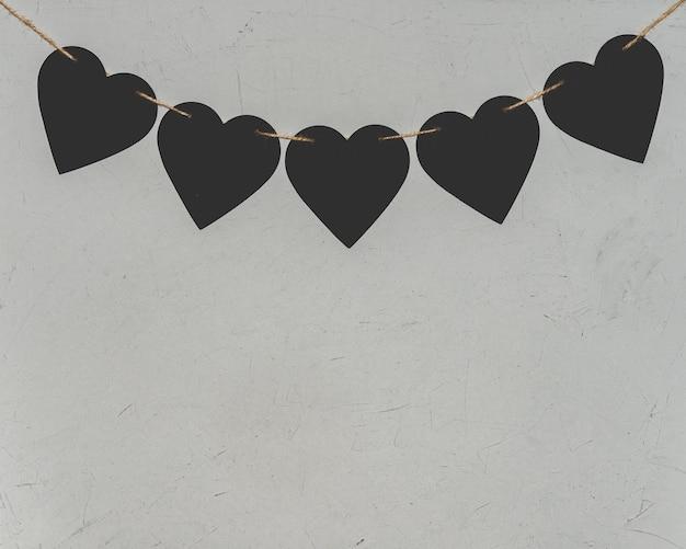 Zwart papier harten op grijze achtergrond. valentijnsdag loft concept.