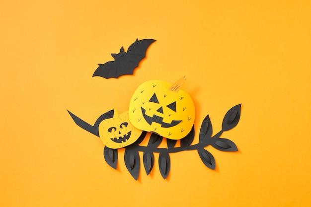 Zwart papier laat tak, vliegende vleermuis en pompoen met een eng gezicht op een oranje achtergrond met ruimte voor tekst. handcraft papier samenstelling naar halloween. plat leggen