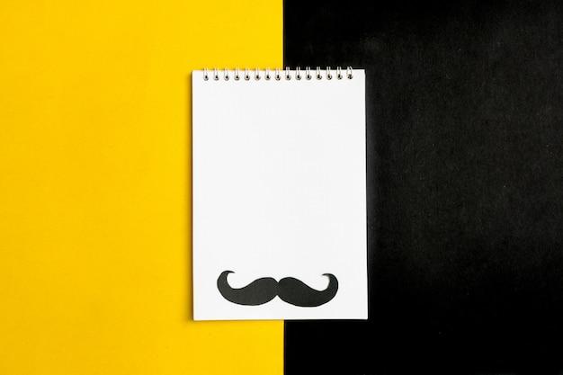 Zwart papier snor, hoed, bril, kladblok op gele achtergrond maand donaties, vaders dag concept