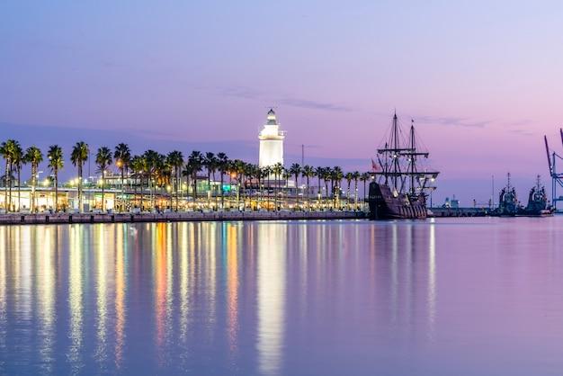 Zwart piratenschip in de haven van malaga met levendige zonsondergangkleuren en vuurtoren