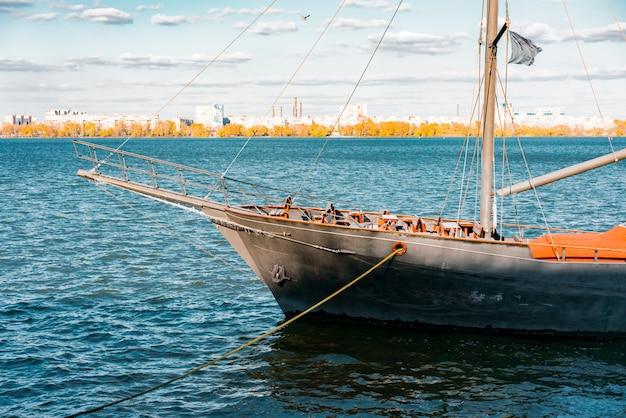 Zwart piratenschip ligt aan de pier. rivier. zee. vervoer. leisure. uitzicht op de stad. stedelijk. loop over de rivier. vaartuig