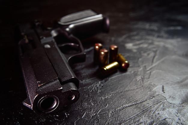 Zwart pistool en kogels op tafelvuurwapens op betonnen achtergrondwapens en munitieconcept van cri...