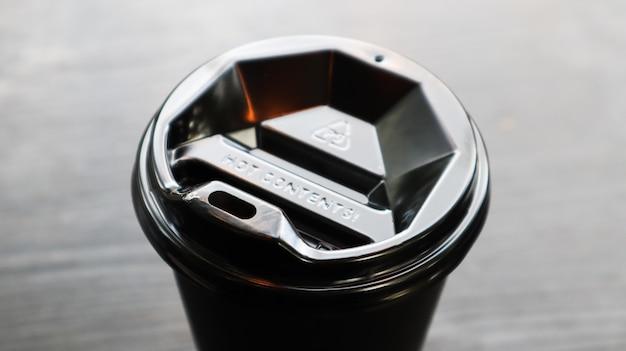 Zwart plastic koffiekopje, bovenaanzicht. afhaalmaaltijden koffiekopje zwarte achtergrond. wegwerp beker close-up op een houten tafel. minimalistische stijl.