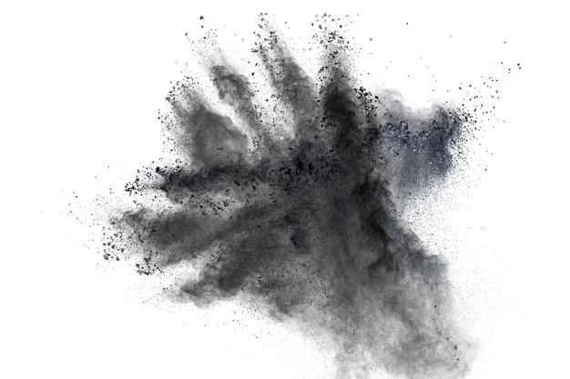 Zwart poeder explosie tegen witte achtergrond. de deeltjes van houtskool spetterde op witte achtergrond.