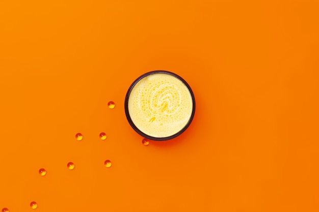 Zwart potje met gele crème met duindoornolie met daarnaast capsules met vitamine e