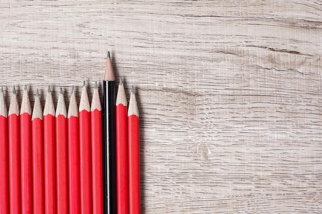 Zwart potlood anders dan de menigte van rode potloden