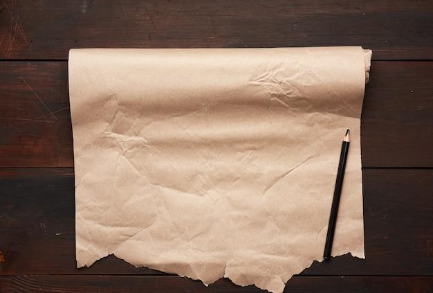 Zwart potlood en rol ongedraaid bruin papier op een houten oppervlak van oude planken