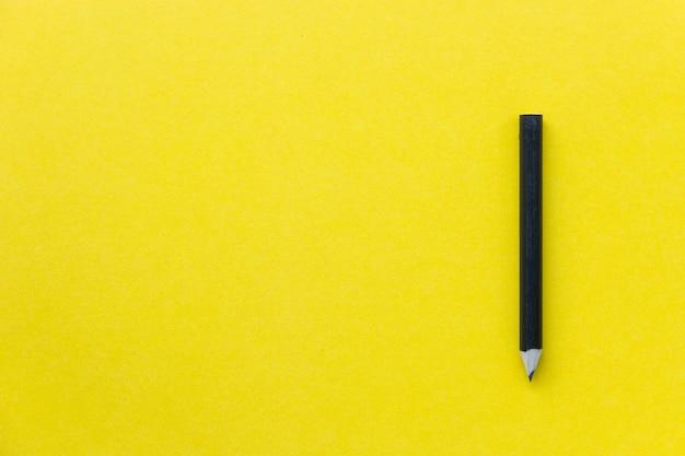 Zwart potlood op gele backgroud, minimalistisch beeld met creatief concept