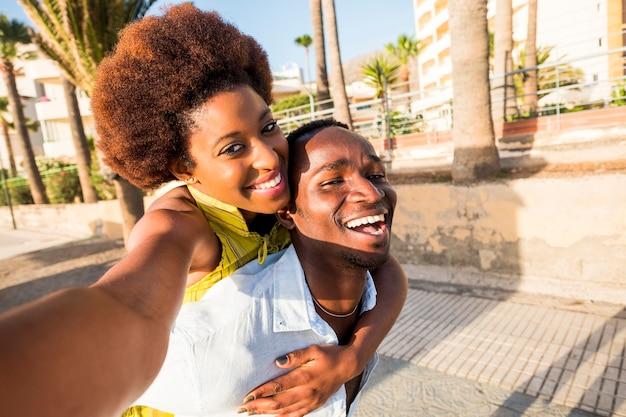 Zwart ras afrikaans amerikaans echtpaar met plezier en een grapje samen spelen op de wandeling in de buurt van het strand. vakantie geluk concept voor twee mooie jonge man en vrouw