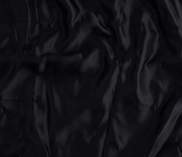 Zwart satijn textiel, stuk stof voor het naaien van gordijnen en zo