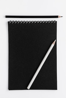Zwart scetchbookmodel en potloden op witte ruimte. bovenaanzicht, kopieer ruimte