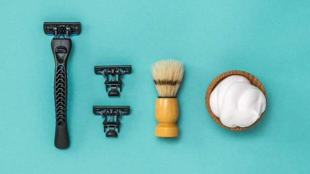 Zwart scheermesje met twee vervangende mesjes en een scheerkwast voor het scheren op een blauwe achtergrond. verzorging van het gezicht van een man. plat leggen.
