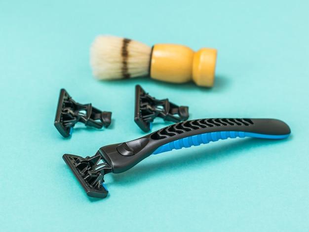 Zwart scheermesje met twee vervangende mesjes en een scheerkwast voor het scheren op een blauwe achtergrond. verzorging van het gezicht van een man.