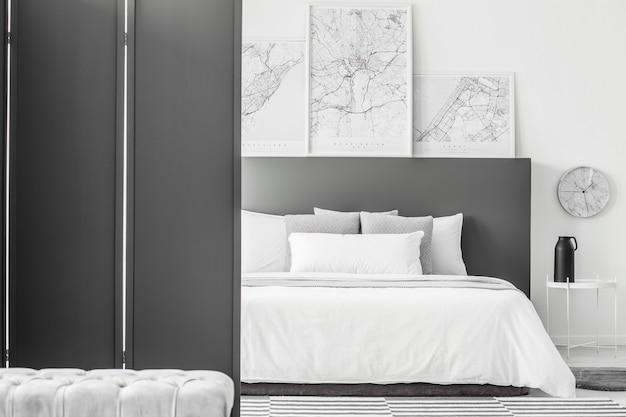 Zwart scherm in minimaal hotelkamerinterieur met kaarten boven bed naast een klok en tafel