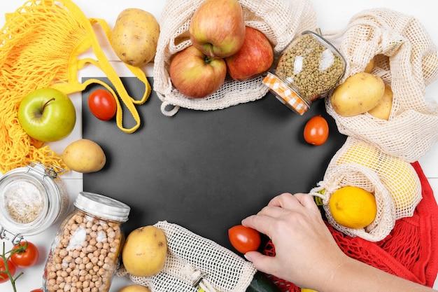 Zwart schoolbord en verschillende groenten in een katoenen ecozak, een netzak en een glazen pot met peulvruchten, gebruik eco-verpakkingen in de keuken, kopieer ruimte
