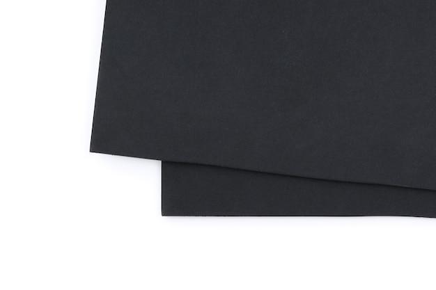 Zwart schuimbord met kleine spatten ligt diagonaal op elkaar, geïsoleerd op een witte achtergrond met kleine schaduwen.