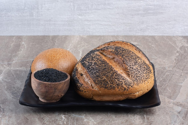 Zwart sesam gecoat brood en een kleine kom zwarte sesamzaadjes op een schotel op marmeren achtergrond. hoge kwaliteit foto