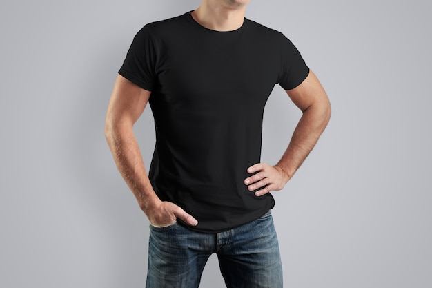 Zwart shirt op een man voor een voorbeeldontwerp. man geïsoleerd op een witte muur.