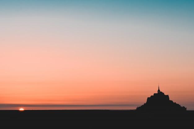 Zwart silhouet van de mont saint michel in een oranje en blauwgroen hemel