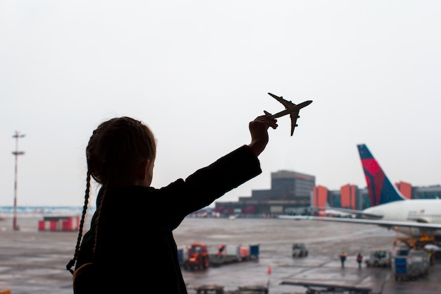 Zwart silhouet van een klein vliegtuig modelstuk speelgoed op luchthaven in kinderenhanden