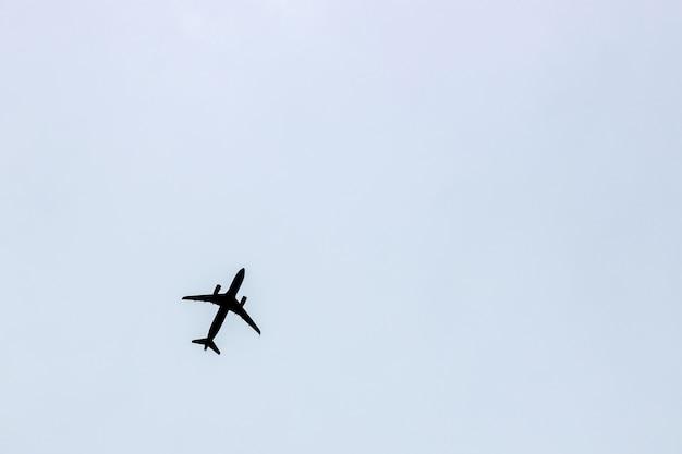 Zwart silhouet van een vliegend vliegtuig tegen een blauwgrijze hemel
