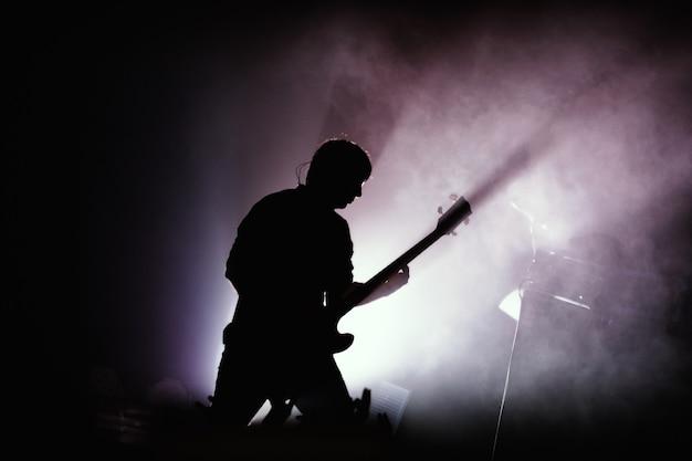 Zwart silhouet van gitarist bij rockconcert