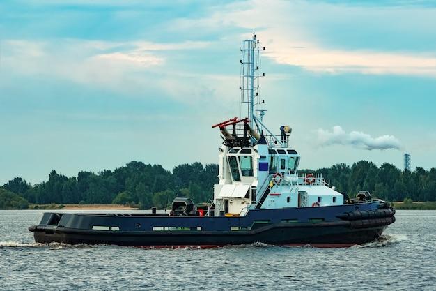 Zwart sleepschip dat naar de vrachtterminal verhuist. industriële service