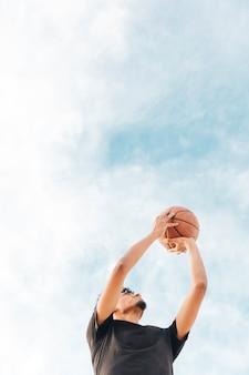 Zwart sportman die basketbal in beweging houdt