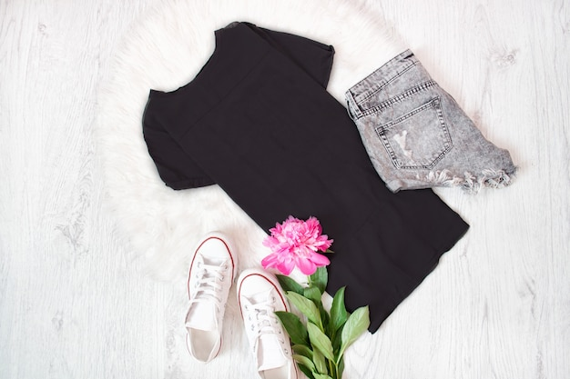 Zwart t-shirt, grijze shorts, witte sneakers en roze pioen. modieus concept