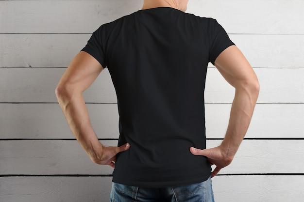 Zwart t-shirt op een sterke man die je handen om je middel houdt op een houten muur. uitzicht vanaf de achterkant.