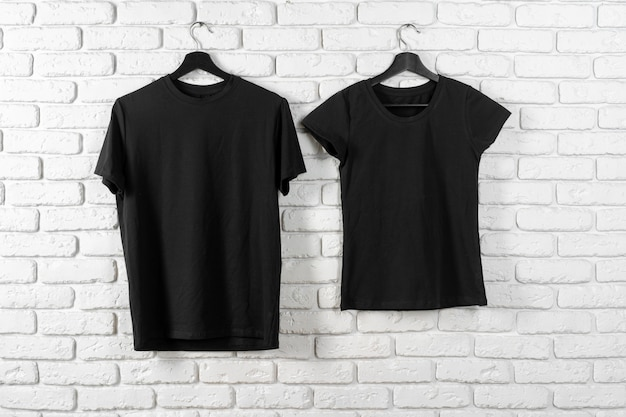 Zwart t-shirt opknoping op een hanger tegen de muur, vooraanzicht