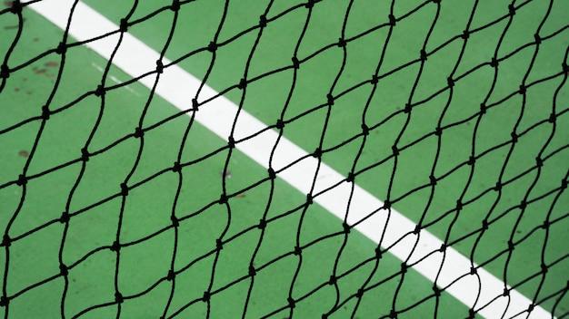 Zwart tennisnet op een groen cementhof