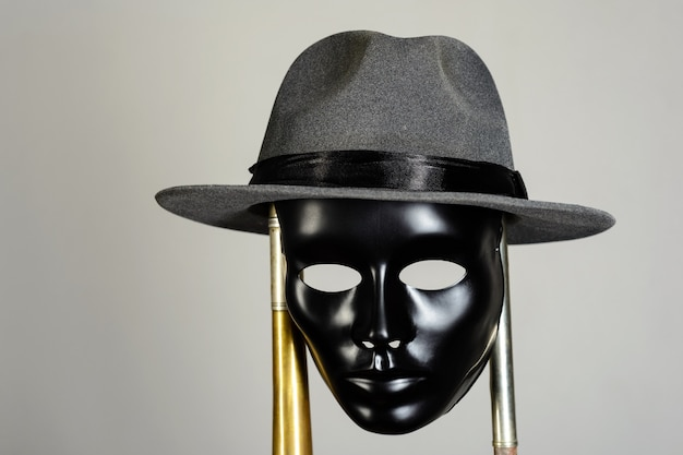 Zwart theatermasker en hoed die op een koperen pijp op grijs hangen