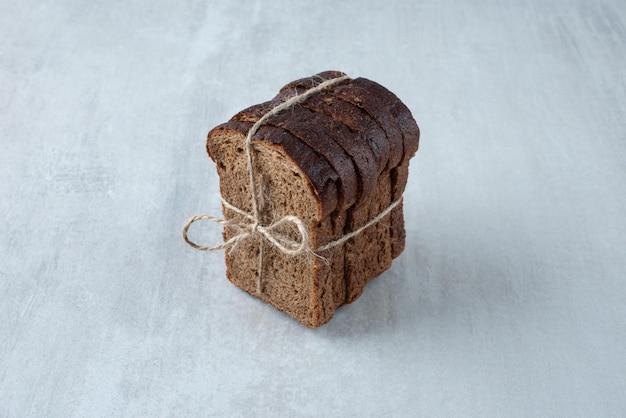 Zwart toastbrood vastgebonden met touw stenen oppervlak.