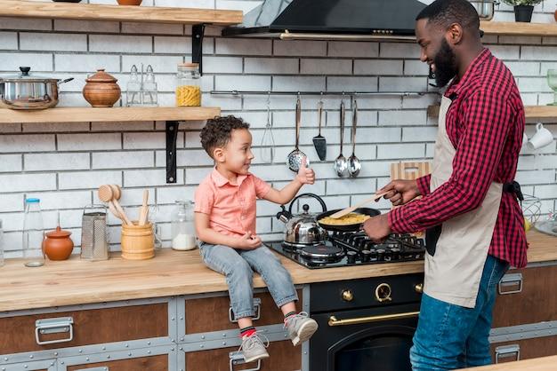 Zwart vader kokend voedsel terwijl zoon die duim toont