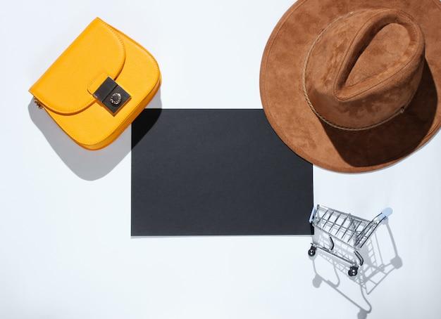 Zwart vel papier voor kopie ruimte, mini winkelwagentje, tas, hoed op grijze tafel. creatieve boodschappentafel
