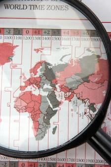 Zwart vergrootglas op wereldkaart met tijdzones