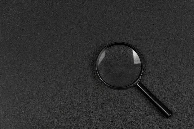 Zwart vergrootglas op zwarte achtergrond. vergrootglas. zoeken