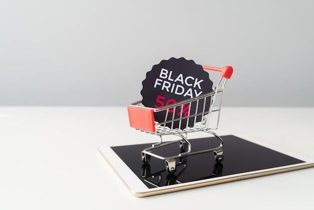 Zwart vrijdagboodschappenwagentje bovenop tablet