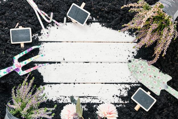 Zwart vuil; plant in bloempot; bloemen; leeg bord; en tuingereedschap over houten bureau
