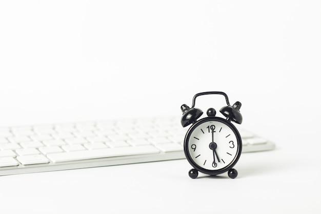 Zwart wekker en toetsenbord op een witte achtergrond. office concept, computerwerk, werkdag, uurloon.