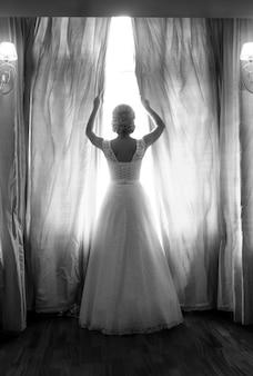 Zwart-wit achteraanzicht van elegante bruid poseren bij groot raam in slaapkamer