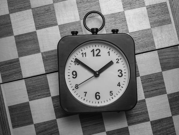 Zwart-wit afbeelding van een klassieke klok op een schaakbord. plat leggen.