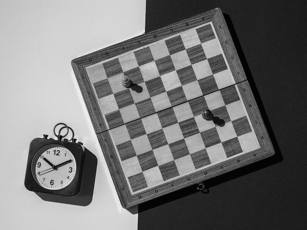 Zwart-wit afbeelding van een schaakbord met stukken en een klok op een zwart-witte achtergrond. het concept van zaken en tijd.