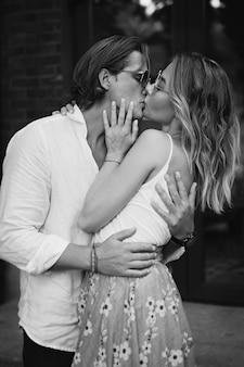 Zwart-wit beeld. close-up romantisch portret van verliefde paar op een date op straat. knappe man en stijlvolle vrouw kussen op donkere achtergrond