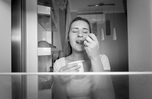 Zwart-wit beeld van binnenuit koelkast op jonge vrouw die 's nachts yoghurt eet