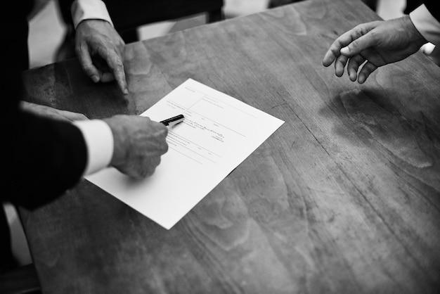 Zwart-wit beeld van bruidegom die de documenten van de huwelijksregistratie ondertekent.