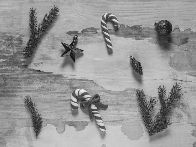 Zwart-wit beeld van christmas speelgoed en snoep op een houten tafel. monochroom.