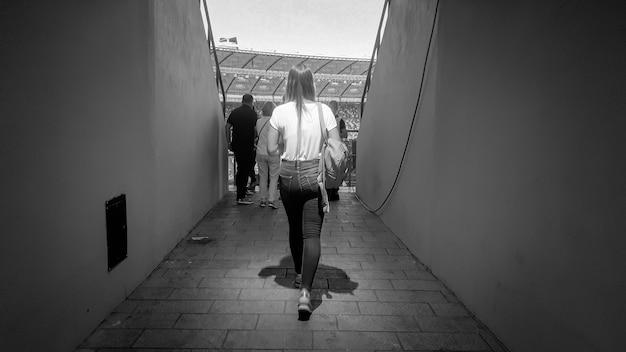 Zwart-wit beeld van de achteraanzicht van een jonge vrouw die door een lange hal in het stadion loopt die leidt naar tribunes en zitplaatsen voor fans.